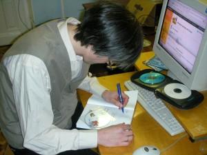 Георгий Курячий подписывает книги для вручения слушателям